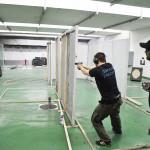 Человек стреляет из пистолета по мишеням в тире МГССК