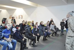 Соревнование по стрельбе среди детей с ограниченными возможностями, дети слушают инструкторов.